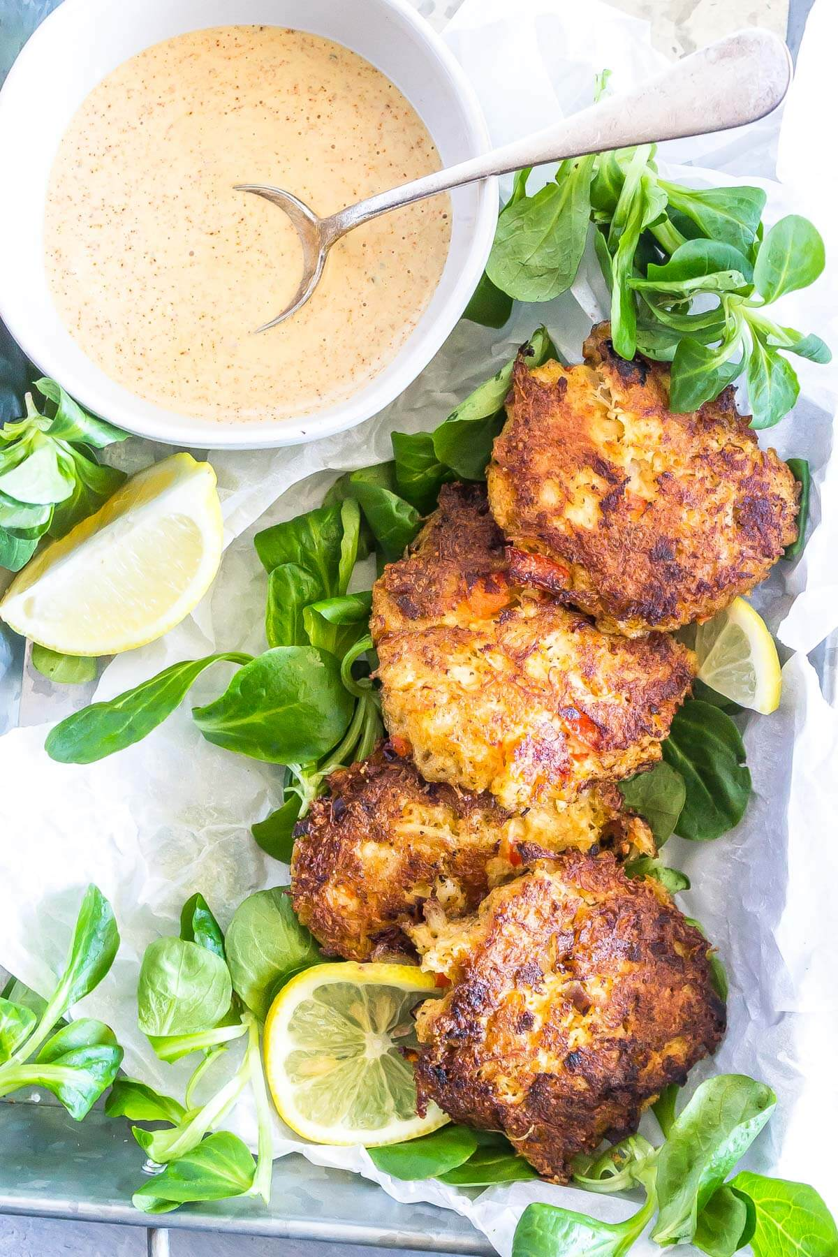 Keto Crab Cakes in tray with sliced lemons and sauce