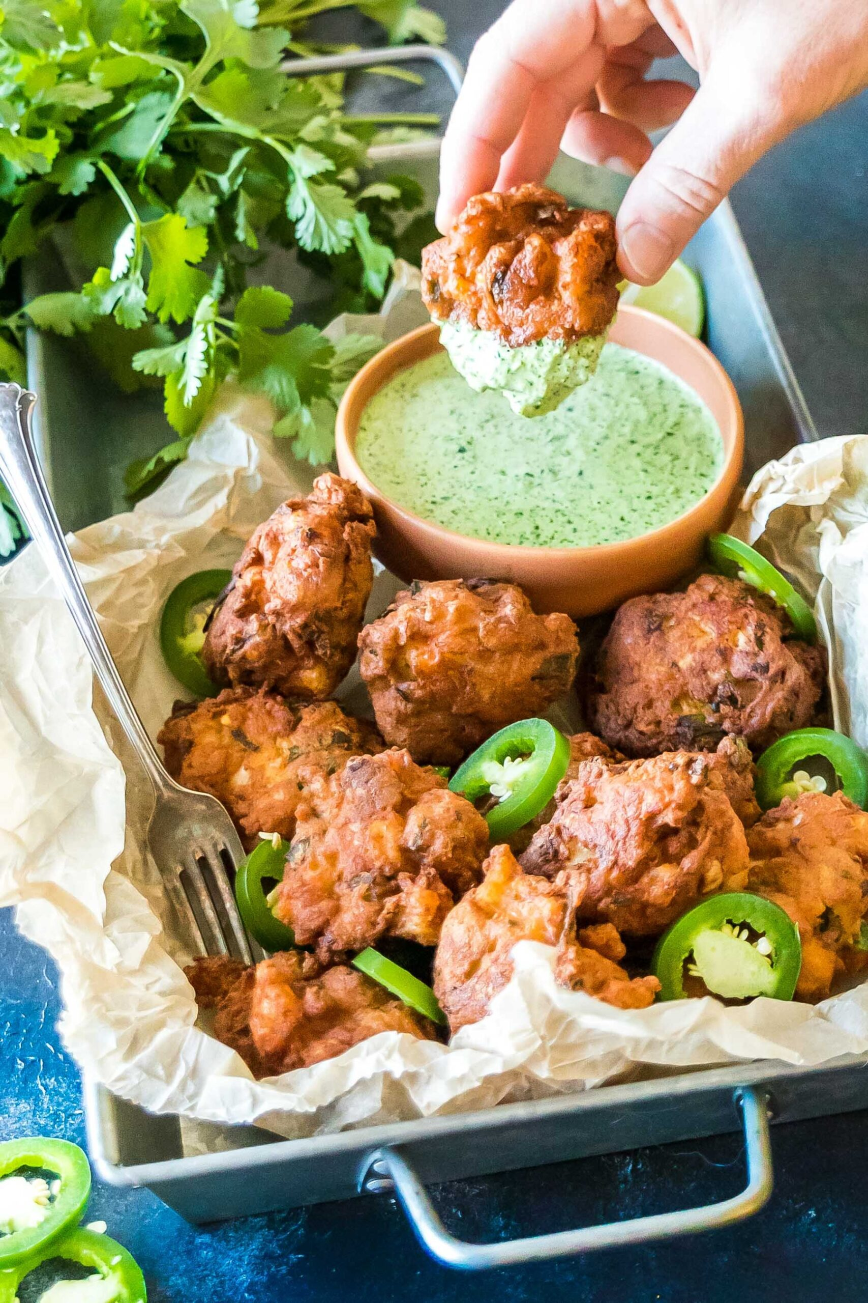 Keto Jalapeño Shrimp Hushpuppies on a tray, one hushpuppy is being dipped into the jalapeno sauce